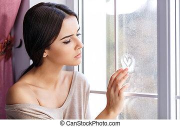 Young woman sitting near window - Love you so much. Pleasant...