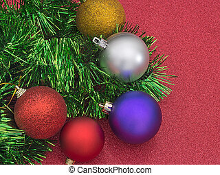 Christmas tree decorations, baubles and tinsel, on glittery red background.