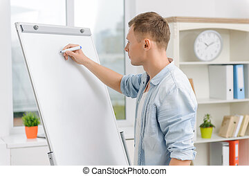 Male executive is writing on whiteboard. - Whiteboard in...
