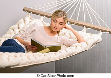 Young girl is reading while lying in the hammock - Favorite...