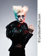 smoking feather - fashion model wearing leather costume with...