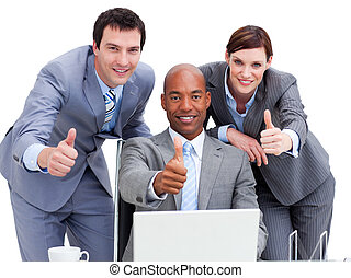 Business people with thumbs up looking at a laptop against a...