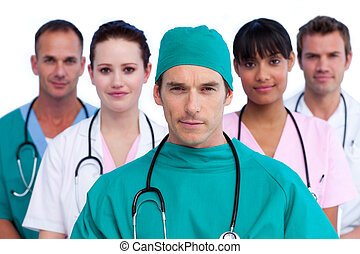 Portrait of a surgeon and his medical team against a white...