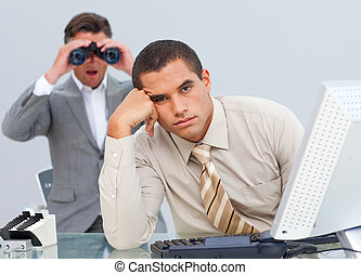 Pensive businessman getting bored and his manager looking through binoculars