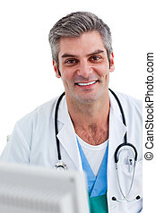 Close-up of male doctor working at a computer against a...