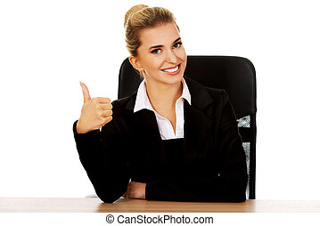 Happy businesswoman shows thumbs up