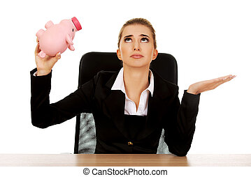 Worried businesswoman with a piggybank behind the desk