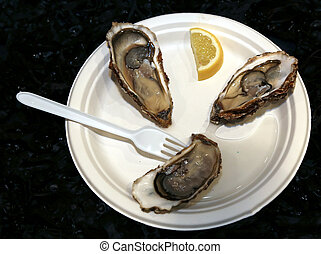 delicious raw oysters served with lemon typical dish of...