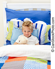 Adorable little boy lying in bed with a teddy bear