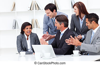 Laughing businesswoman applauded by her team in the office