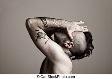 suffer - tattooed young man suffering.his hands on his face.