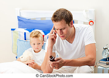 Attentive father giving cough syrup to his sick son sitting...