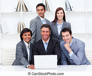 Multi-ethnic team working at a laptop in their office