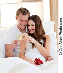 Cheerful couple drinking champagne with strawberries lying...