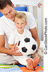Cute little boy and his father playing with a soccer ball...
