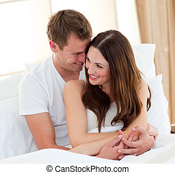 Romantic lovers embracing lying in bed at home