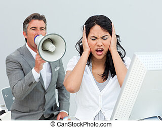 Furious manager shouting through a megaphone in a colleague\'s ea
