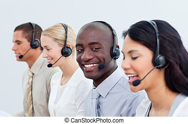 Ethnic man and his team working in a call center in a...