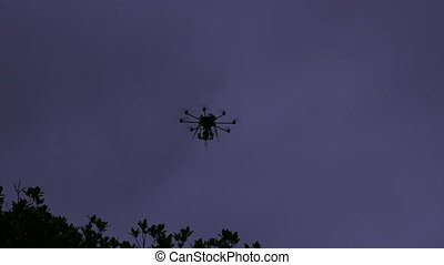 Drone fly in air - Silhouette of a Drone fly in air at dusk.