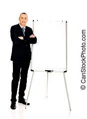 Male executive standing near flip chart - Mature businessman...