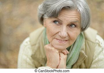 Happy elderly woman enjoying in autumn park