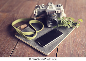 Vintage camera, blank smartphone, diary and leaves on wooden...