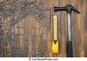 house repair, house shape with hammer and  tape measure
