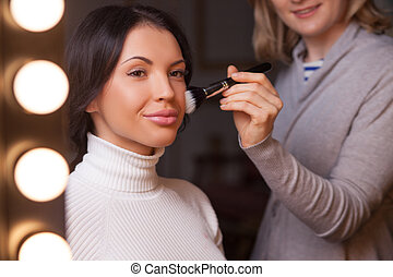 Experienced female visagiste is making the lady beautiful -...