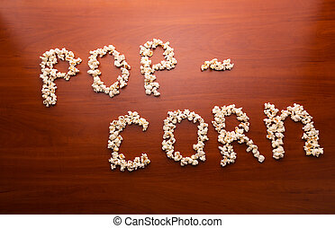 "Ppcorn on the table - Popcorn forming the word ""pop-corn"" on..."