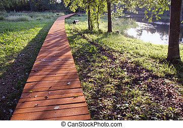 Wooden pavement by the lake - Wooden sidewalk by the lake in...