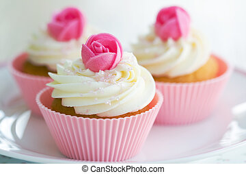 Rosebud cupcakes - Cupcakes decorated with frosting and pink...