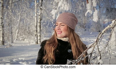 Close up of a beautiful woman is happy and walks in the park on a winter day