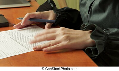 Woman signs a document.