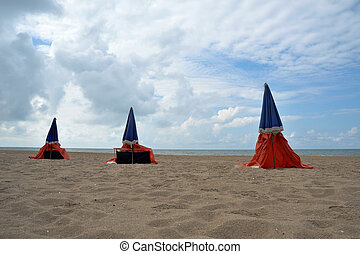 Beach in cold weather, with three closed sunshades