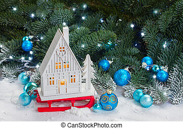 White christmas house on sledge with blue decorations in...