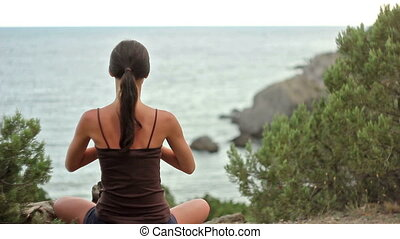 Fitness brunette girl doing yoga by the seaside with relaxing mountain view