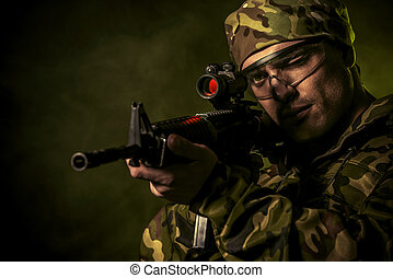 commando - A soldier in war paint looks through the scope of...