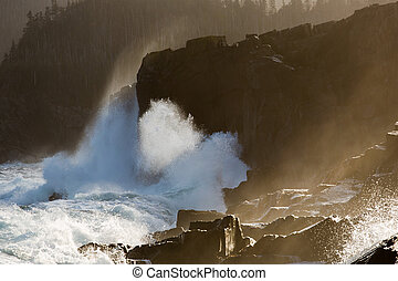 Waves breaking over rocks along the - Large waves breaking...