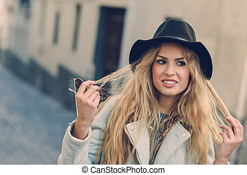 Woman looking with her curly blonde hair in urban background