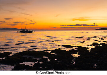 outrigger boat during sunset - traditional philippine bangka...