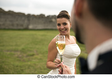 bridal couple clink glasses of champagne on the nature