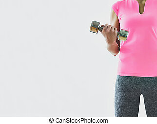 Anonymous sexy woman training with dumbbells, white...
