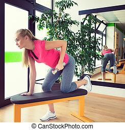 Attractive young woman training in gym with dumbbells in front of a mirror