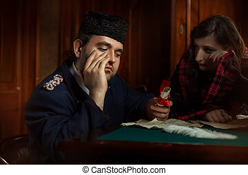 Man and woman in retro style weep over the manuscripts. The...