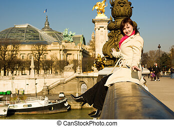 Playful beautiful woman in Paris sitting on the balustrade of the Pont Alexandre III