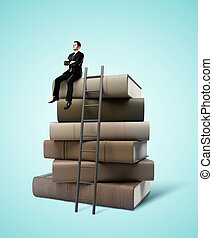 man sitting on stack of books - businessman sitting on stack...