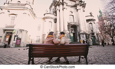 Young couple sit on bench