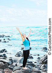Biracial teen girl on rocks by ocean praising God - Slim,...