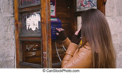 Pretty young woman talking on the phone in telephone booth