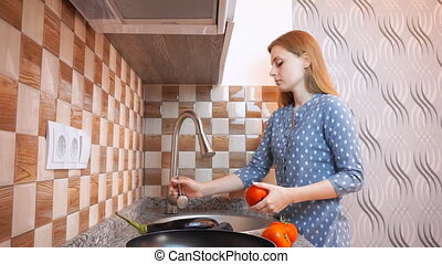 Healthy food lifestyle: beautiful woman casually cooking, washing vegetables at kitchen. Wide shot, handheld, slow motion 60 fps.